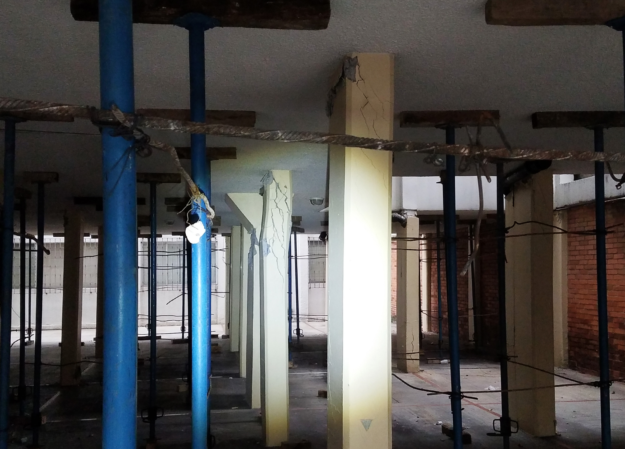 The failure of buckled first floor columns at 609 Calle Azores, Mexico City, MX illuminated by flashlight
